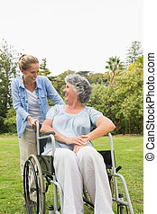 Happy mature woman in wheelchair talking with daughter in...