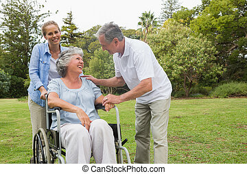 Happy woman in wheelchair with husband and daughter talking...