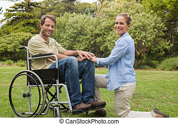 Handsome man in wheelchair with partner kneeling beside him...