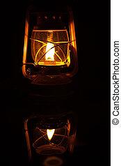 Storm Lantern - Yellow storm lantern burning at night on a...