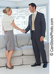 Cheerful business people shaking hands in bright office