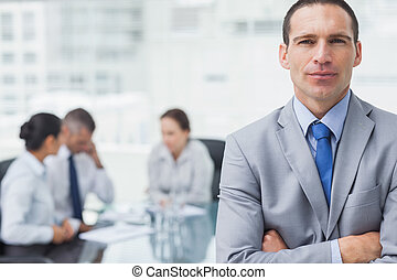 Serious businessman posing with coworkers on background -...