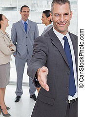 Cheerful businessman introducing himself holding out his...
