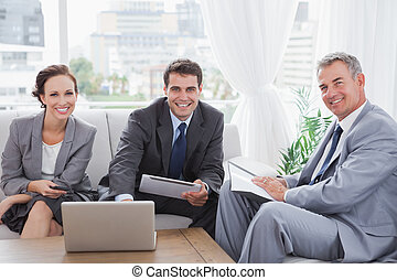 Business people smiling at camera while having a meeting in...