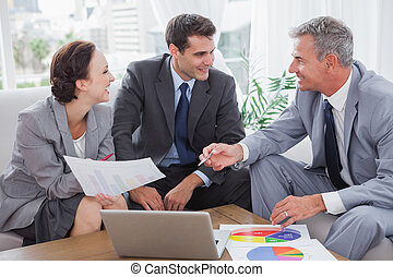 Cheerful business people analyzing financial graphs of their...