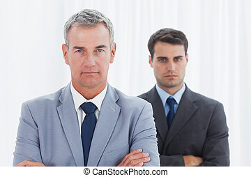 Stern businessmen posing crossing arms in bright office
