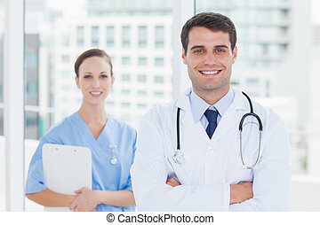 Smiling surgeon and doctor posing together in bright office