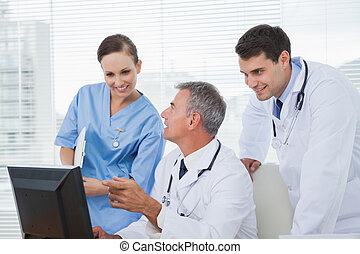 Cheerful doctors and surgeon working together on computer in...