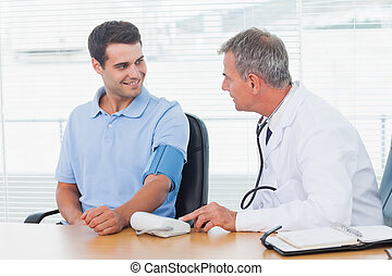 Doctor taking blood pressure of smiling patient