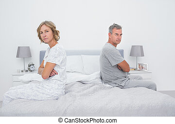 Couple sitting on different sides of bed not talking after...
