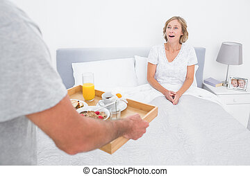 Husband bringing breakfast in bed to surprised wife in...