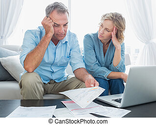 Worried couple using their laptop to pay their bills at home...