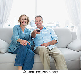 Content middle aged couple sitting on the couch watching tv...