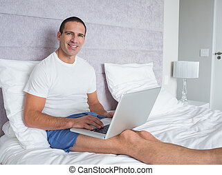 Happy man using laptop on bed smiling at camera at home in...