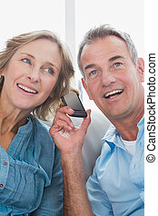 Smiling couple listening to mobile phone together