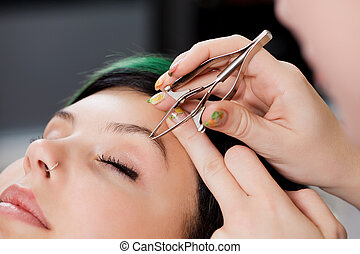 Hairdresser's Hands Using Tweezers On Woman's Eyebrow -...
