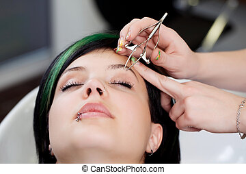 plucking eyebrow - young woman gets her eyebrows plucked in...