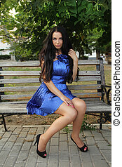 Beautiful brunette woman wearing in blue dress resting on bench over park. Outdoors Portrait.