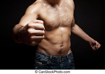 Young shirtless muscular man - young man beats his fist