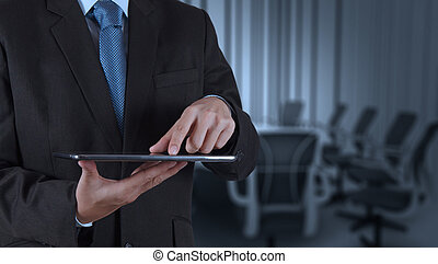businessman hand using tablet computer and board room