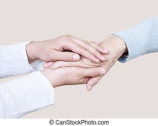 helping hands - hands of a young woman holding the hand of...
