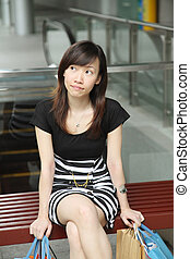 Asian Female Shopper Sitting