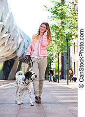 Woman walking dog and talking to friends on mobile phone -...