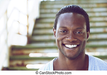 Portrait of an african american man smiling outdoors -...