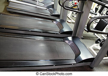 Treadmills in a row woth various sport items on background