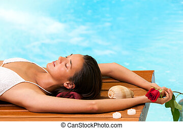 Woman relaxing next to swimming pool.