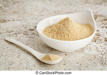 maca root powder - a small bowl with a spoon against ceramic...
