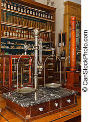 old medical scales against the cabinet with the drugs in the...