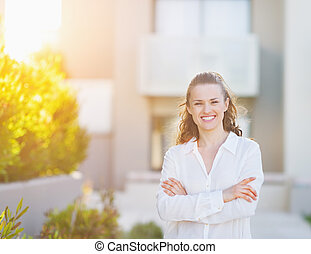 Portrait of smiling young woman standing in front of house...