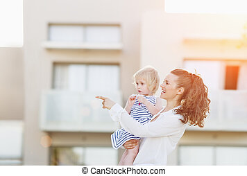 Happy mother with baby standing in front of house building...