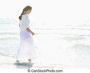 Young woman walking into sea