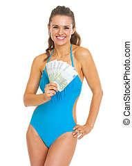 Smiling young woman in swimsuit showing fan of euros