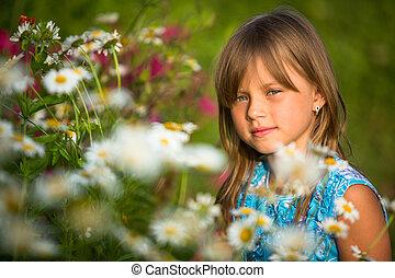 Little beautiful girl outdoor among wildflowers