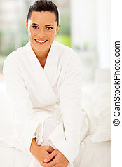 fresh young woman in bathrobe sitting on bed