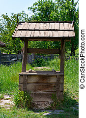 Old village well with a wood roof with green garden on...