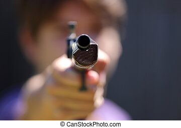 Gun - A close up view of someone pointing a gun at the...