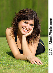 Portrait of a beautiful happy woman lying on the lawn of a park