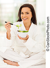 woman sitting on bed eating green salad