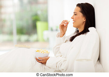 young woman sitting on bed eating popcorn and watching tv -...