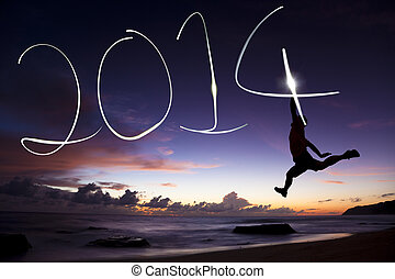 happy new year 2014.young man jumping and drawing 2014 by...