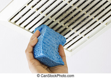 Cleaning Bathroom Fan Vent Cover with Sponge - Close up...