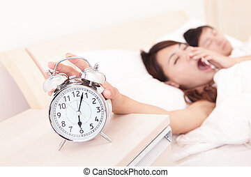 Wake up - Tired couple touch the alarm clock while they are...