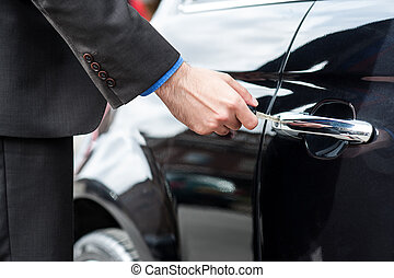 Man inserting car key into the door lock - Man unlocking the...