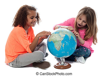 Young girls locating countries on globe - Elementary school...