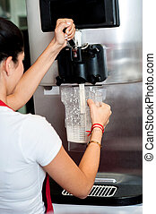 Woman operating machine to pour thick shake - Process of...