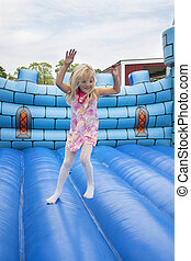 Child in bouncing castle - A 6 year old girl having fun on a...